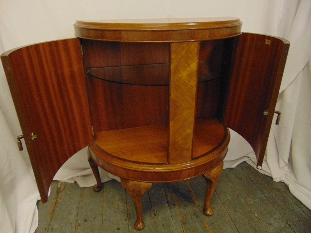Lot 5 - A mahogany and satinwood demi-lune cabinet with hinged doors on four scroll legs