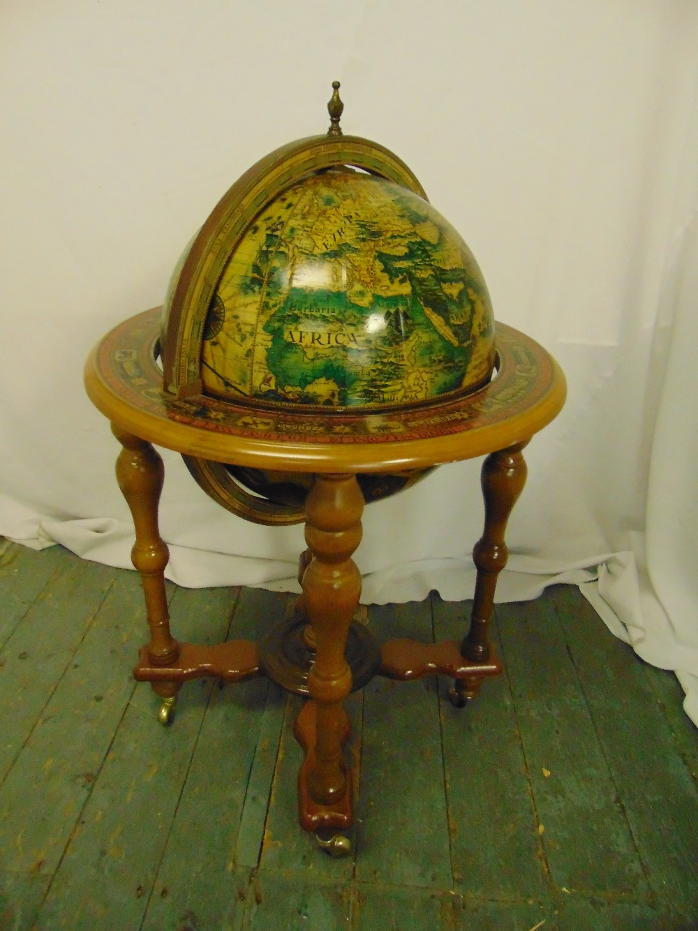 Lot 20 - A globe drinks stand on four turned legs and castors, 96cm (h)