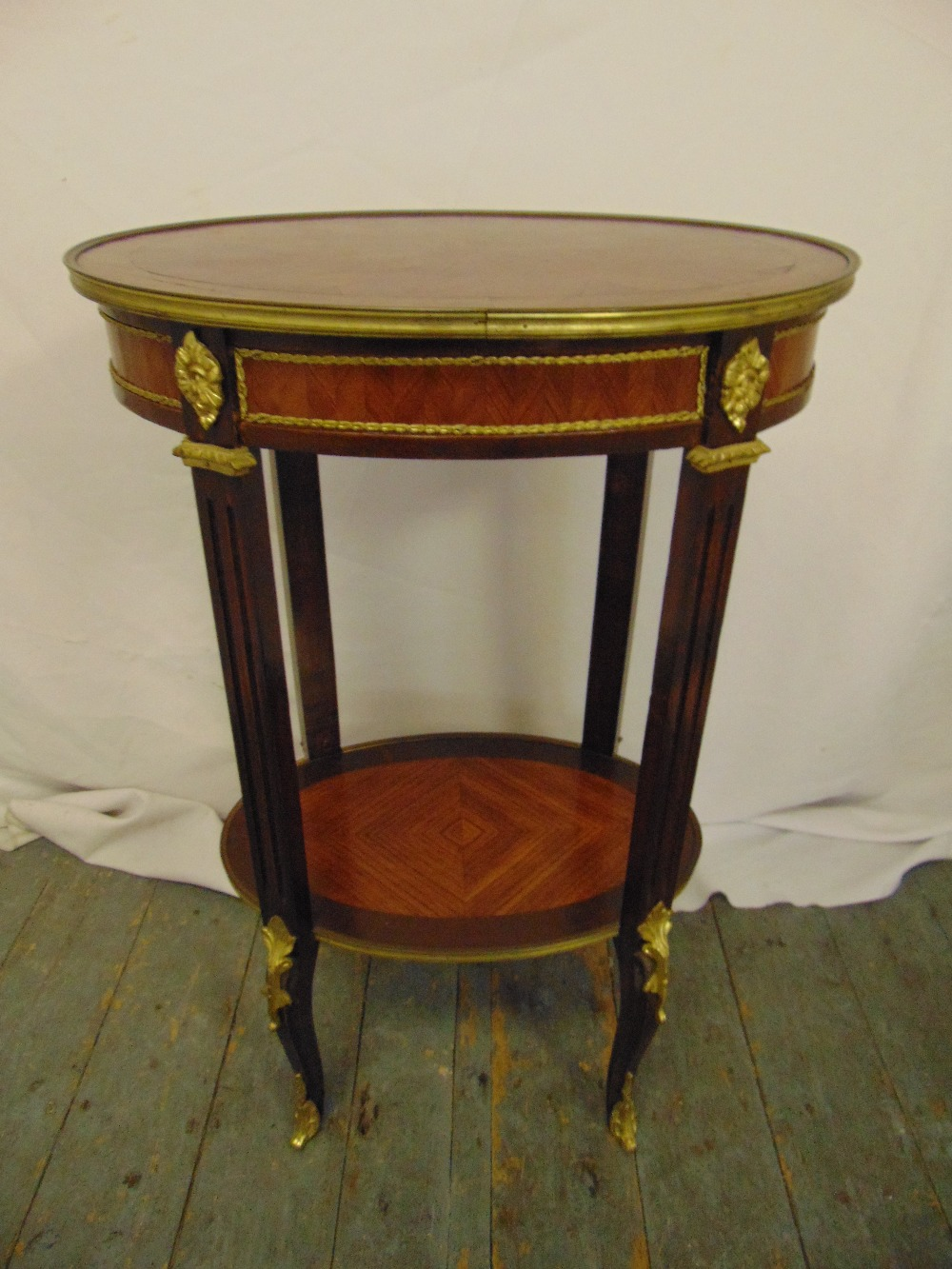 Lot 6 - A French oval mahogany, kingwood parquetry and gilt metal occasional table on four cabriole legs, 77