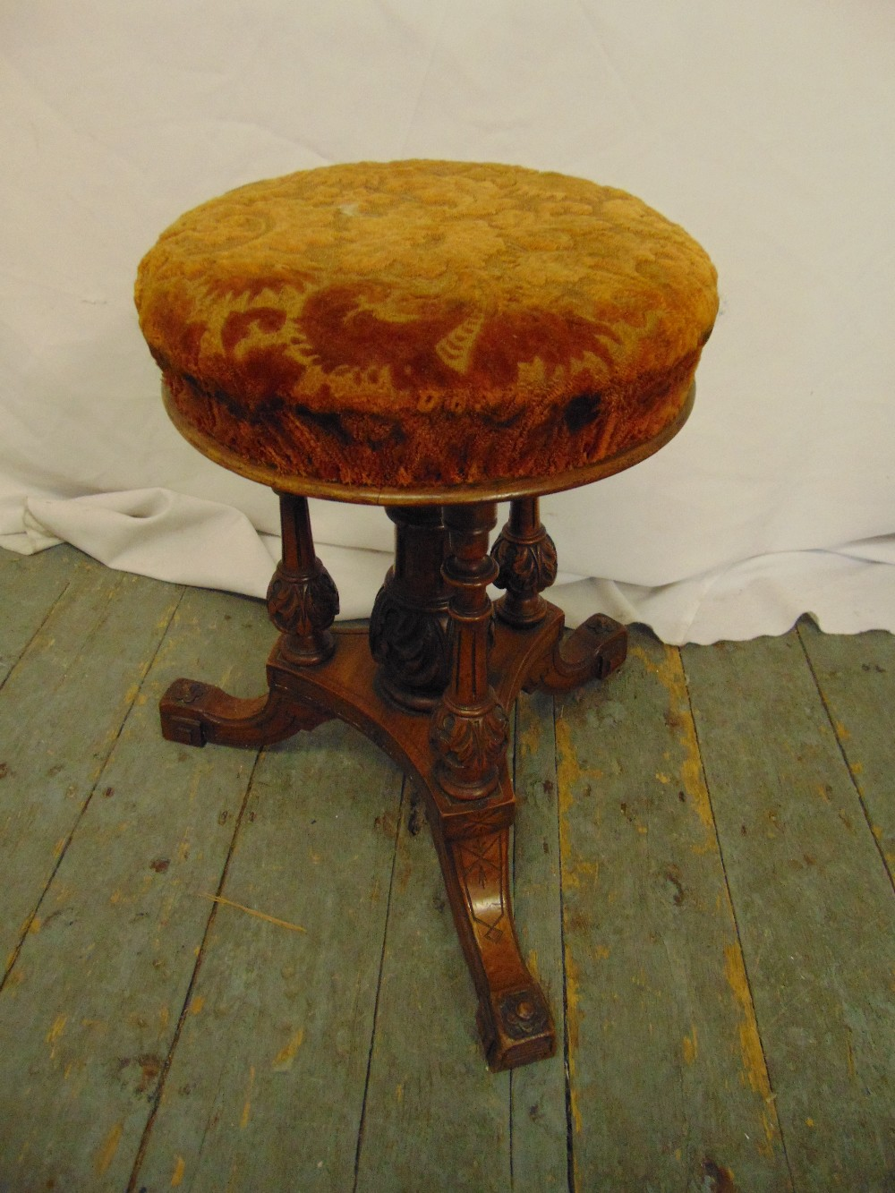 Lot 18 - An oak piano stool with upholstered seat on triform base