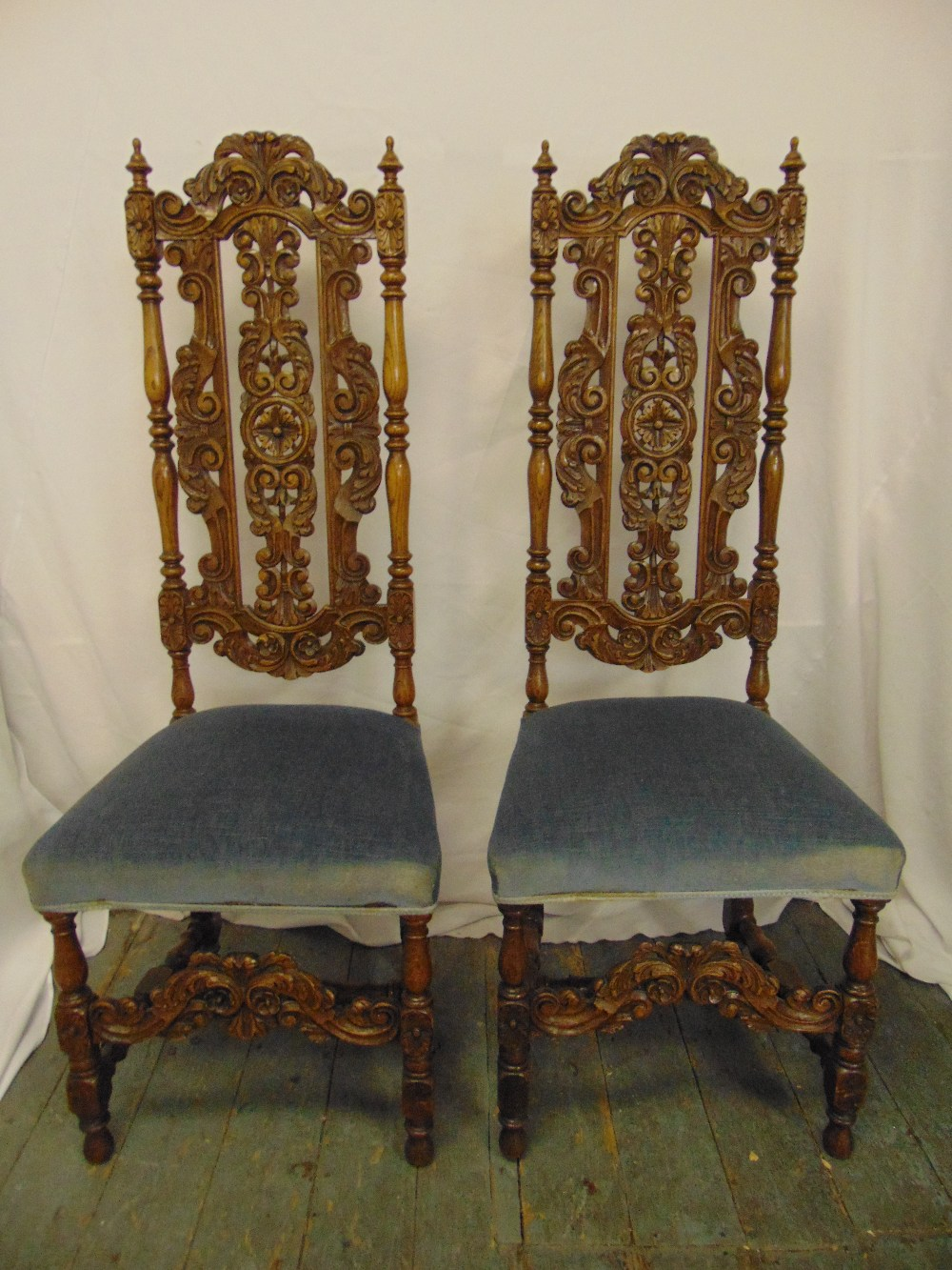 Lot 14 - A pair of continental profusely carved and pierced high back upholstered occasional chairs on four