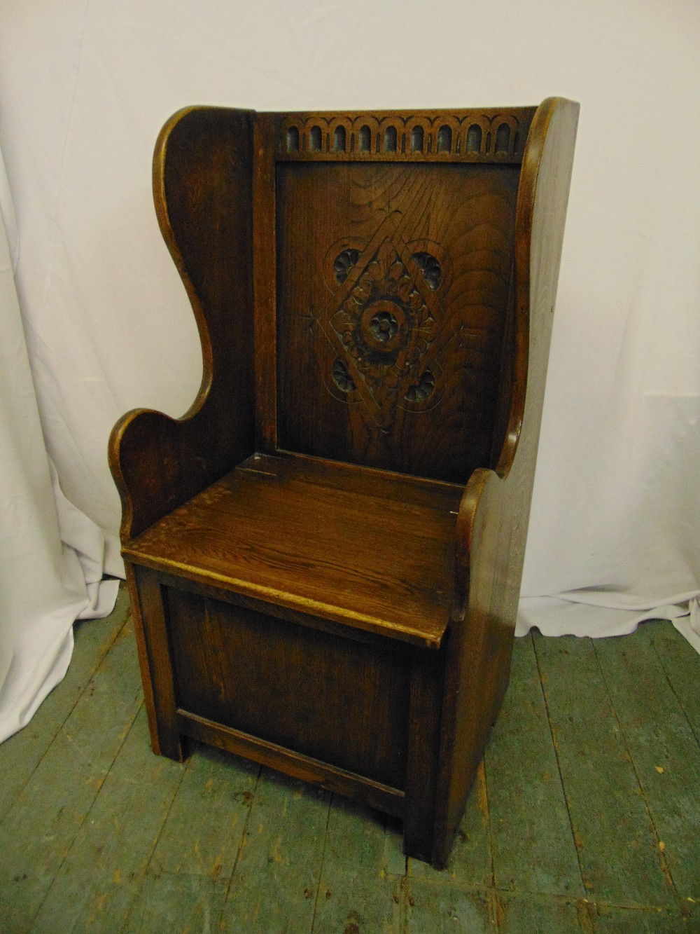 Lot 17 - An oak monks bench with carved back and hinged seat, 107 x 55.5 x 45cm