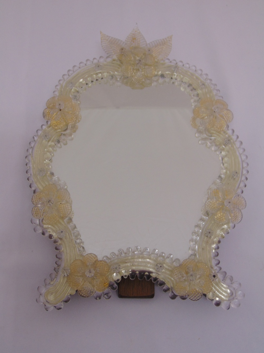 Lot 26 - A Venetian shaped glass decorative table mirror with hinged back strut, 40cm (h)