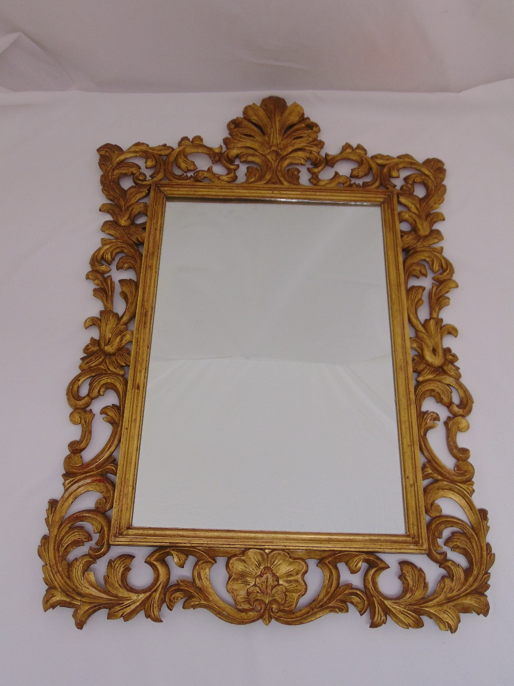 Lot 23 - A gilded wooden rectangular, leaf and shell carved wall mirror in the Rococo style, 100 x 68.5cm