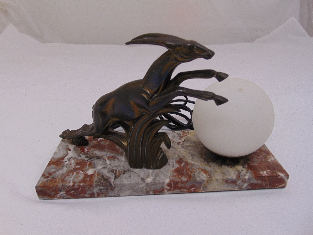 Lot 31 - A bronze Art Deco table lamp of globular form with leaping gazelle on a rectangular marble base,