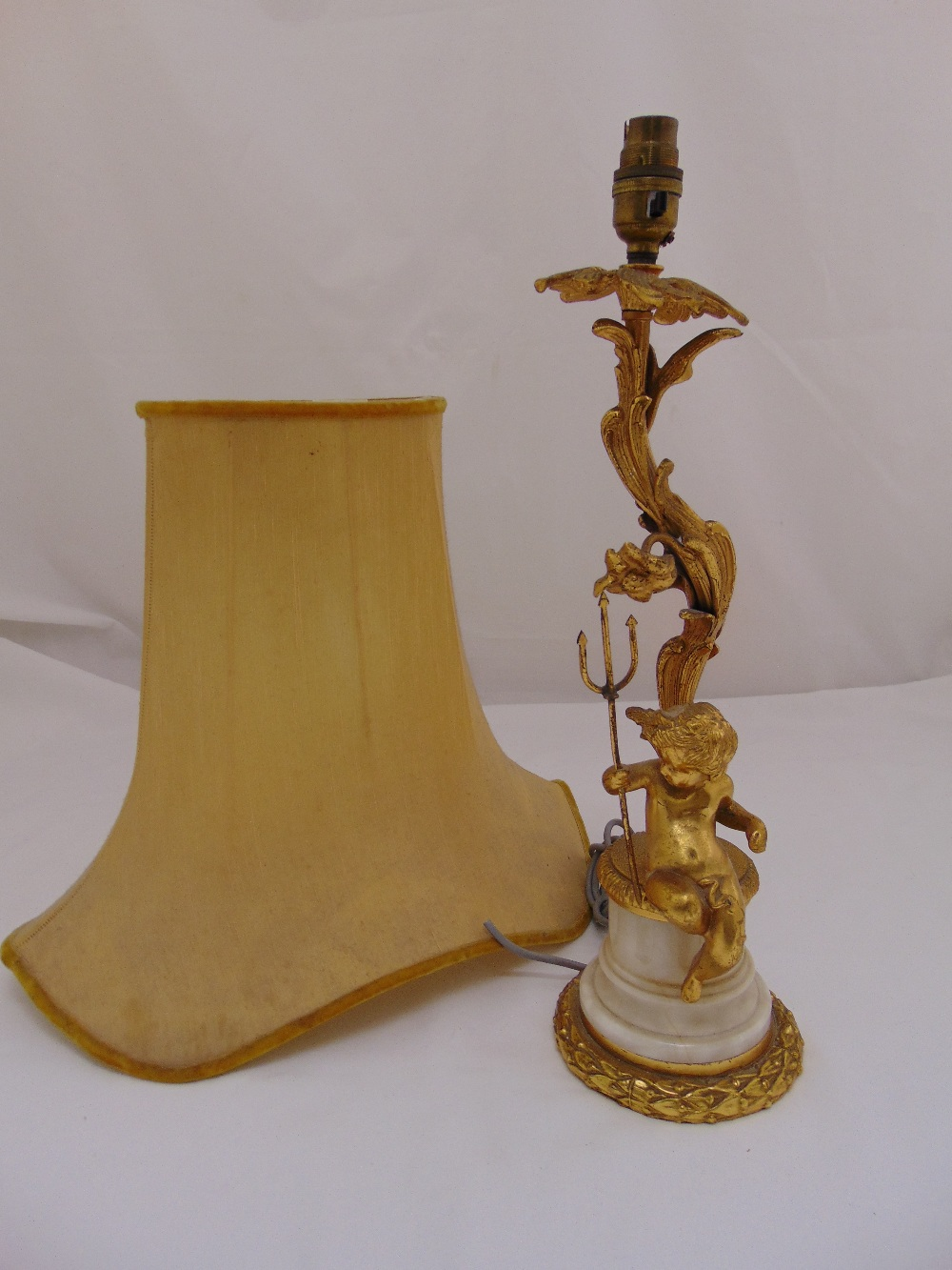 Lot 30 - An ormolu and marble table lamp with applied putti holding a trident on tapering cylindrical base to