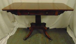 A Regency drop leaf mahogany Pembroke table on quadriform base with brass paw feet, 75 x 120.5