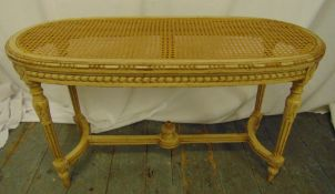 A French oval bergere stool with hand painted detail on four tapering fluted legs, 51 x 90 x 38cm