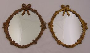 A pair of 19th century wall mirrors with ormolu frames of leaves and flowers surmounted by