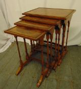 A nest of four rectangular burr walnut side tables on turned tubular supports and outswept bracket