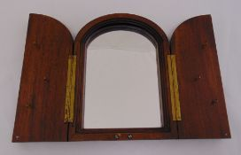 A mahogany wall mirror, arched top the hinged doors set with key hooks, 30 x 22cm