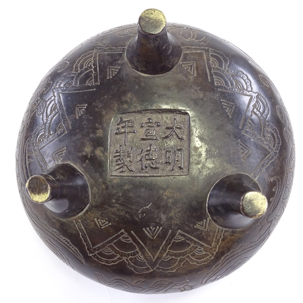 Lot 25 - A Chinese patinated bronze 2-handled Ding incense burner, with incised decoration and 6 character