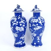A pair of Chinese blue and white porcelain prunus pattern baluster vases and covers, 4 character