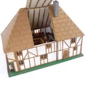 A handmade model Tudor design doll's house, complete with contents and hinged openings, height 21cm