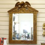 A modern gilt-framed bevelled-edge wall mirror, floral decorated frame surmounted by an eagle,