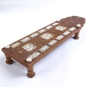 A Chinese 19th century relief carved wood games board, with inset carved ivory panels, on turned