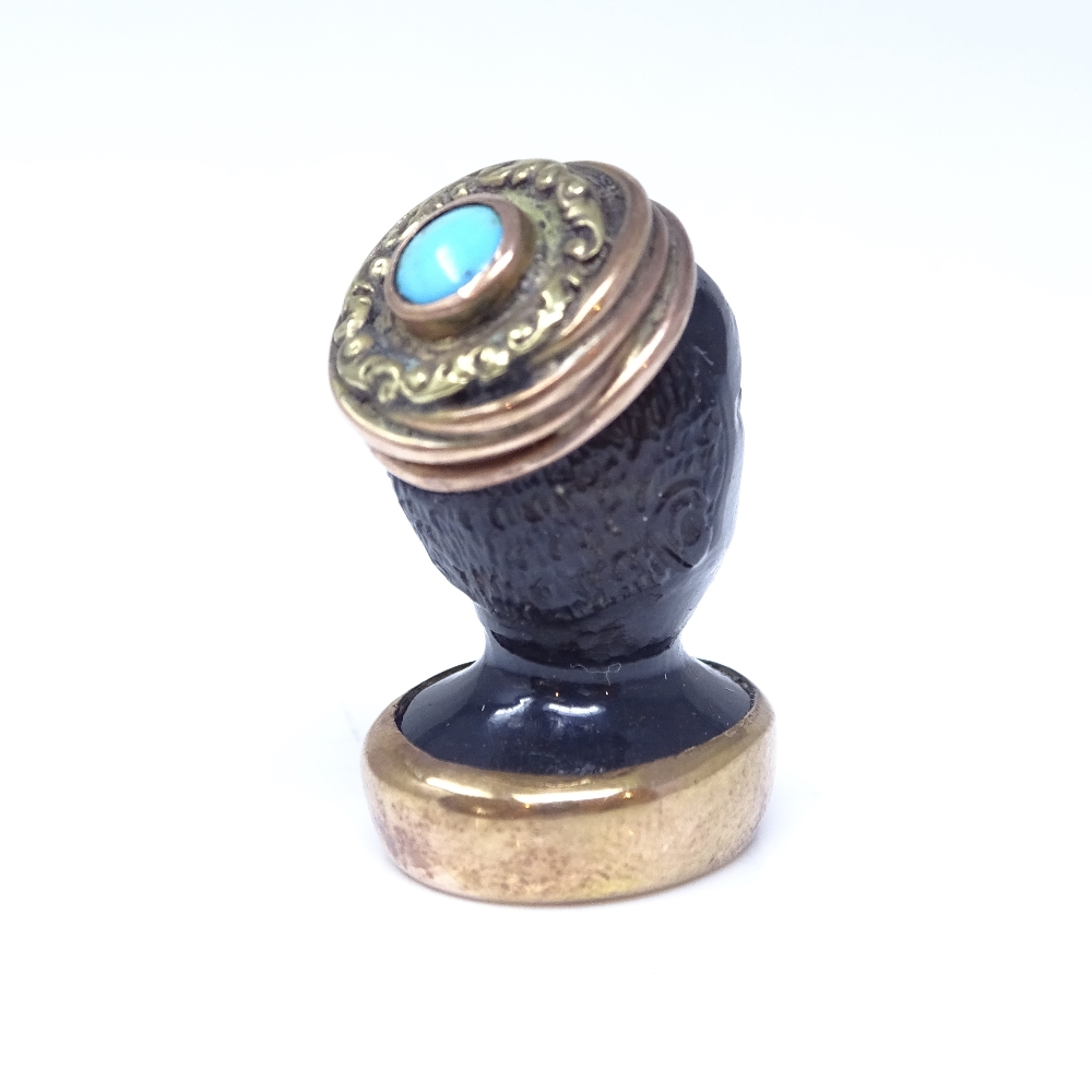 Lot 94 - A 19th century banded agate figural Blackamoor seal fob, unmarked rose gold mounts with cabochon