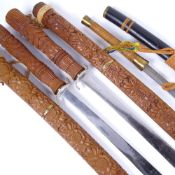 A pair of Oriental swords in carved wood scabbards, with carved handles, length 91cm, and an
