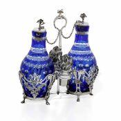 Oliera in argento fuso, sbalzato e cesellato con bottiglie in vetro blu molato. [...]