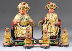 A Pair of Chinese Carved Polychrome and Gilt Wood Seated Figures of Female Goddesses Wearing