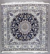 A Nain Carpet, Modern, woven in pastel colours with a bold central floral shaped medallion,