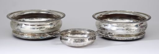 A Pair of Elizabeth II Silver Circular Coasters and a George V Silver Lemon Strainer, the coasters