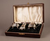 GEORGE V CASED THREE PIECE SILVER CONDIMENT SET, of bellied form with cyma borders and scroll