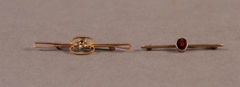 9ct GOLD BAR BROOCH collet set with an oval garnet and a 9ct GOLD OPEN WORK BAR BROOCH with centre