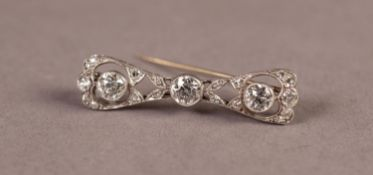 DIAMOND BOW SHAPED OPEN WORK BROOCH, collet set with three round, old cut diamonds, the centre stone
