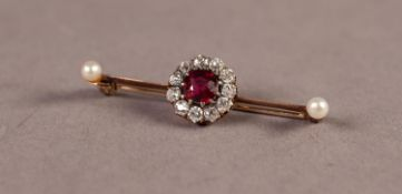 BAR BROOCH WITH CENTRE RUBY AND DIAMOND CLUSTER AND TWO END SMALL PEARLS, the centre ruby cushion