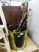 A COPPER COAL SCUTTLE WITH SWING HANDLE AND A SET OF THREE LONG BRASS FIRE APPLIANCES