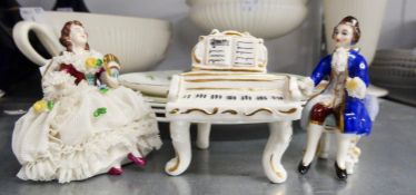 A MODERN DRESDEN CHINA GROUP OF THREE PIECES, VIZ A COURTIER SEATED TO PLAY, A PIANO AND A SEATED