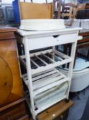 A WHITE PAINTED WOOD KITCHEN WORK TROLLEY WITH DRAWER, A WINE RACK AND TWO SLOTTED UNDERSHELVES; FOR