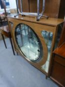 A WOOD EFFECT DISPLAY CABINET WITH GLASS SLIDING DOORS TO THE CIRCULAR FRONT APERTURE