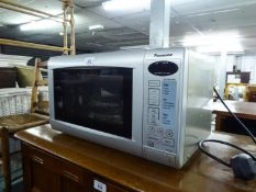PANASONIC GREY CASED MICROWAVE; DELONGI FACETED BLACK CASED FOUR SLOT TOASTER AND A MATCHING JUG