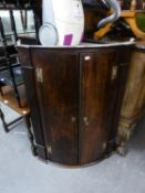 AN ANTIQUE OAK BOW FRONTED CORNER CUPBOARD