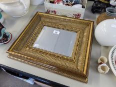 A SMALL RECTANGULAR BEVELLED EDGE WALL MIRROR IN GILT FRAME