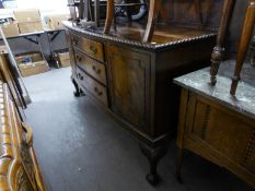AN EDWARDIAN MAHOGANY BOW FRONT SIDEBOARD, HAVING TWO CUPBOARD DOORS, THREE CENTRAL DRAWERS ON