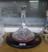 A STERLING HAND CUT CRYSTAL SHIP?S DECANTER, ON MAHOGANY CIRCULAR TWO HANDLED TRAY STAND