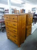 A CONTINENTAL POLISHED HARDWOOD TALL BOY CHEST OF FIVE LONG DRAWERS, ON HEAVY TURNED FEET AND A PAIR
