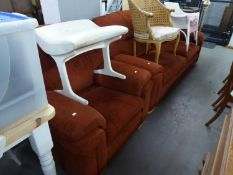 A LOUNGE SUITE OF TWO PIECES COVERED IN MAROON FABRIC COMPRISING A THREE SEATER SETTEE WITH FOUR