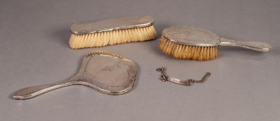 GEORGE V SILVER BACKED DRESSING TABLE HAND MIRROR AND MATCHING HAIRBRUSH, engraved with floral