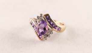 9ct GOLD, AMEHTYST AND DIAMOND CROSS-OVER RING set with a centre oval amethyst and twelve tiny