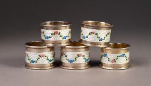 GEORGE V SET OF FIVE SILVER AND GUILLOCHE ENAMELLED NAPKIN RINGS, each painted with floral swags