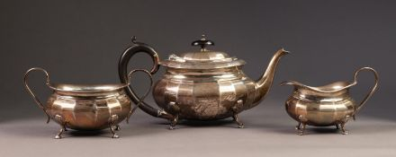 INTER-WAR YEARS THREE PIECE SILVER TEA SERVICE of oval panelled form, the teapot with black wood