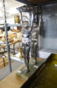 TWO IDENTICAL ART DECO STYLE PLATED METAL NUDE FIGURES OF YOUNG WOMEN HOLDING ALOFT BASKETS OF