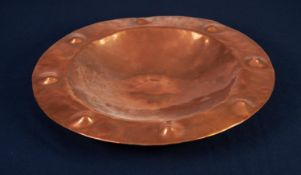 ARTS AND CRAFTS PLANISHED COPPER PLAQUE, of circular form with dished centre and raised, circular