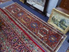 PERSIAN RUNNER, the red field with seven pole medallions, three with latch hook surrounds, the