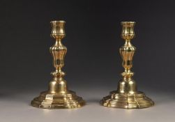 PAIR OF ANTIQUE BRASS CONTINENTAL CANDLESTICKS, with campana shaped sconces, lobed melon shaped