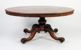VICTORIAN FIGURED AND CARVED MAHOGANY LOO TABLE, the moulded, oval, flame , tilt-top above a